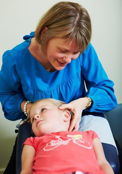 global chiropractic doing head massage for child