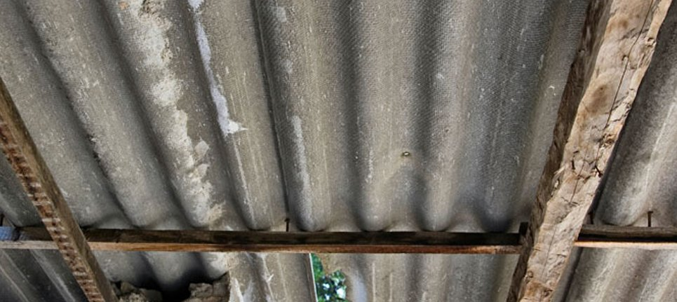 A close up of a roof made of corrugated metal that may contain asbestos