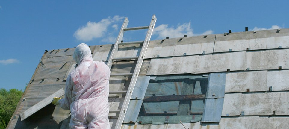 An asbestos specialist working on a roof