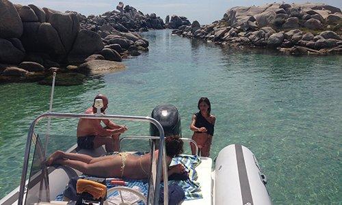 una donna e un uomo su un gommone e un'altra in piedi in acqua