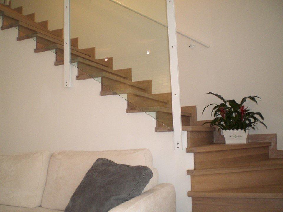 scala da interni in muratura rivestite in legno con corrimano di appoggio in metallo e struttura in vetro