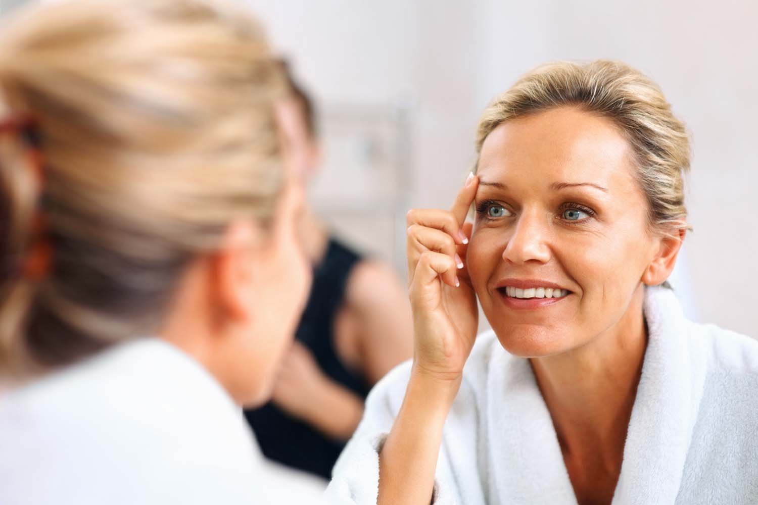 Woman looking at beauty results in mirror