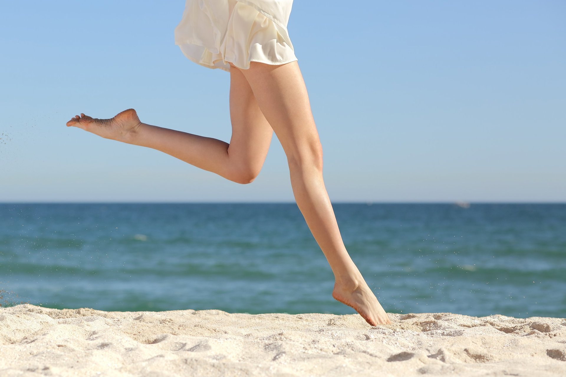 lady jumping at a beach