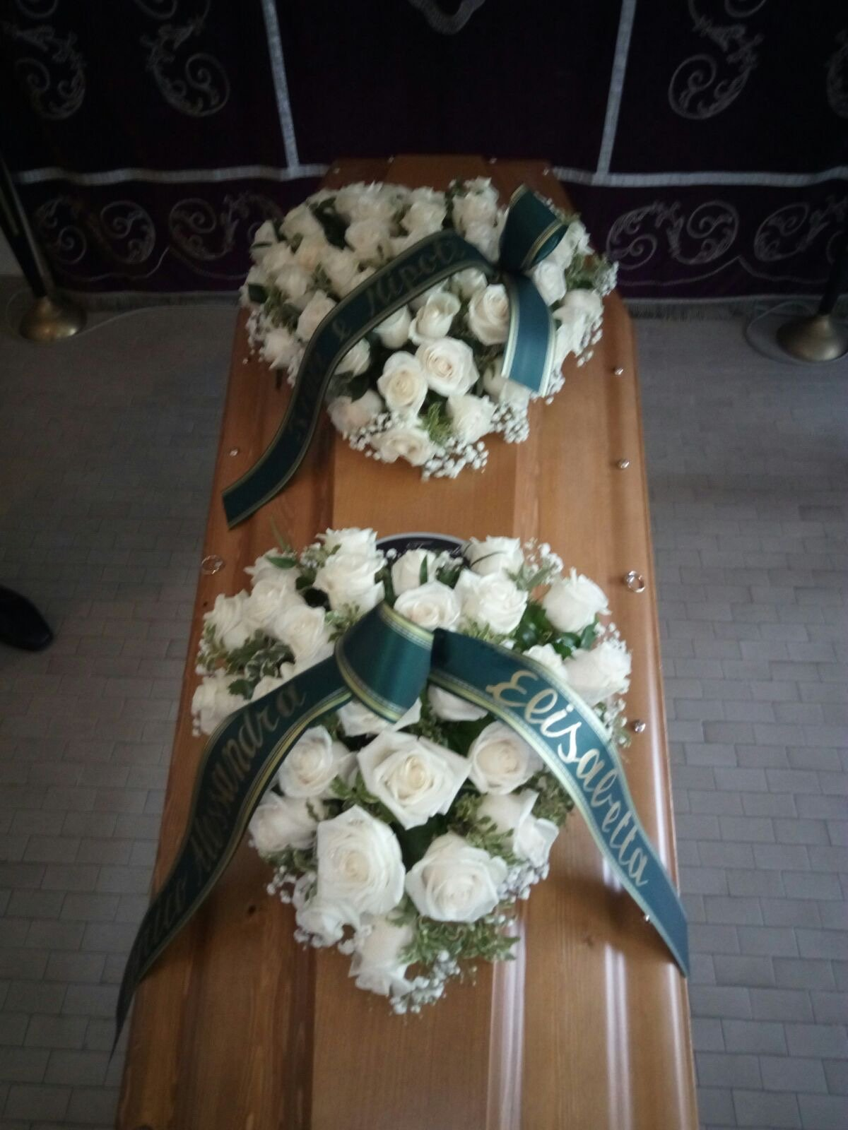due composizioni di fiori a forma di cuore sopra una bara funebre