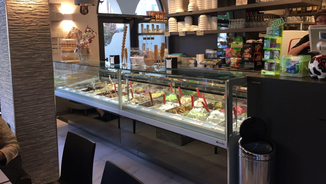 Inquadratura interna a una gelateria con banco frigorifero con gelati