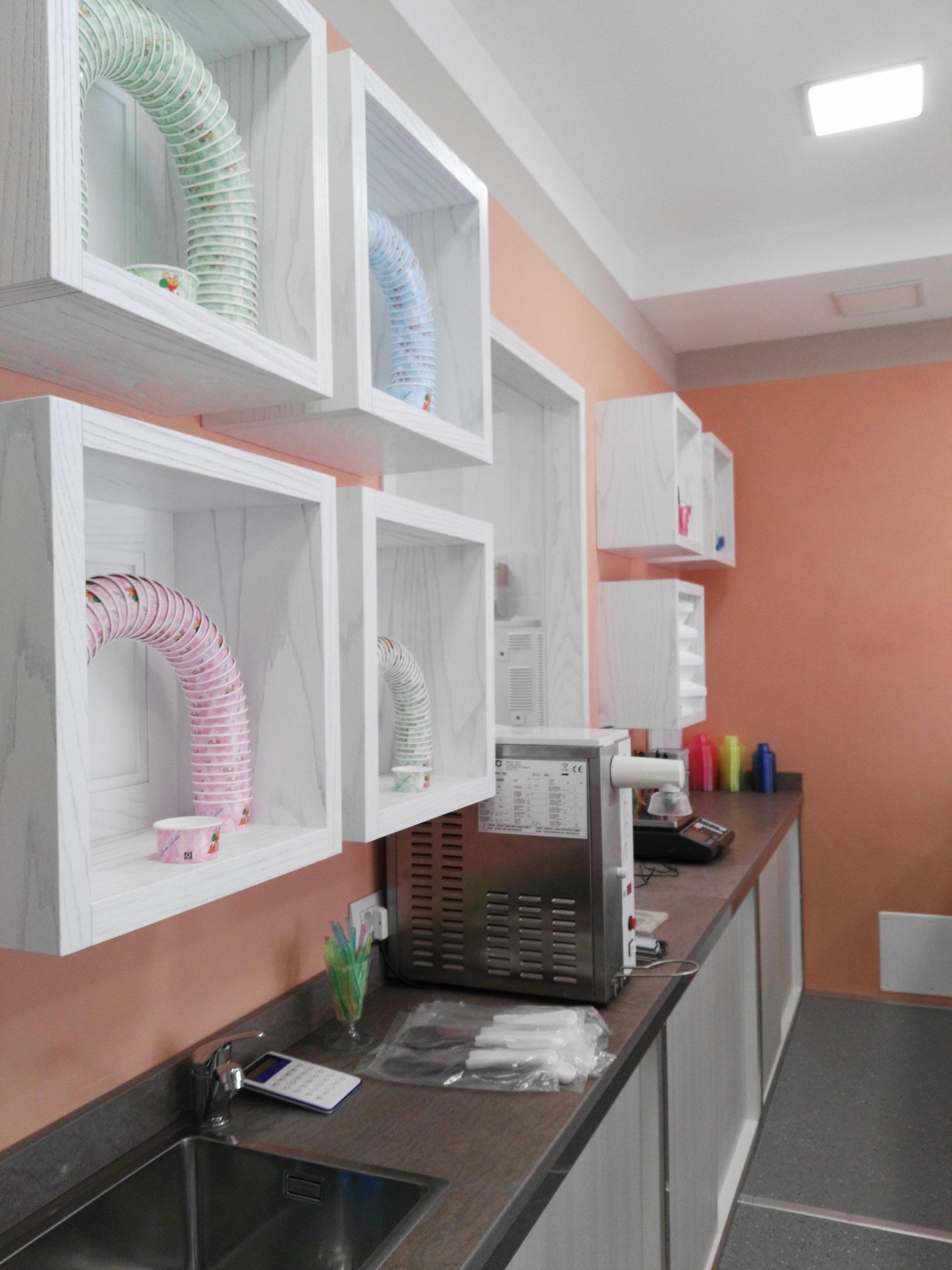 Vista laterale del banco della gelateria ed espositori con coppette