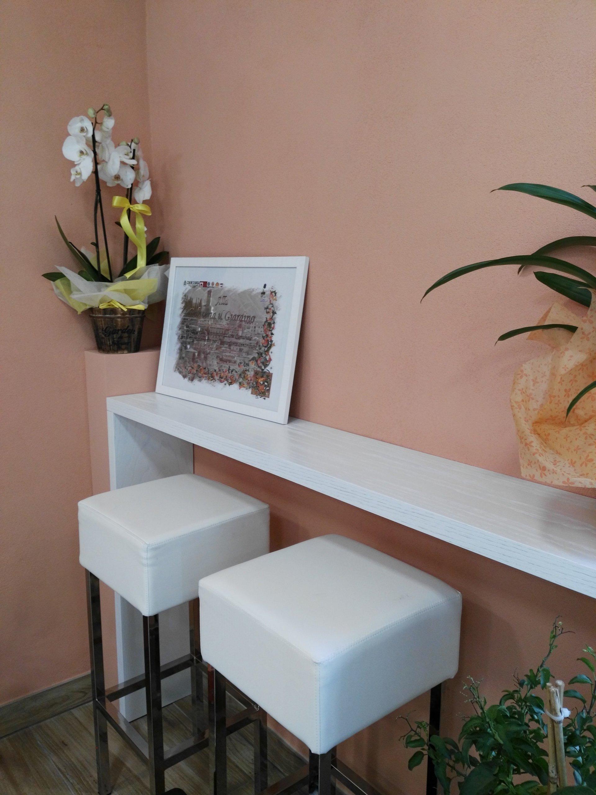 Interno della gelateria con tavolo e sgabelli bianchi