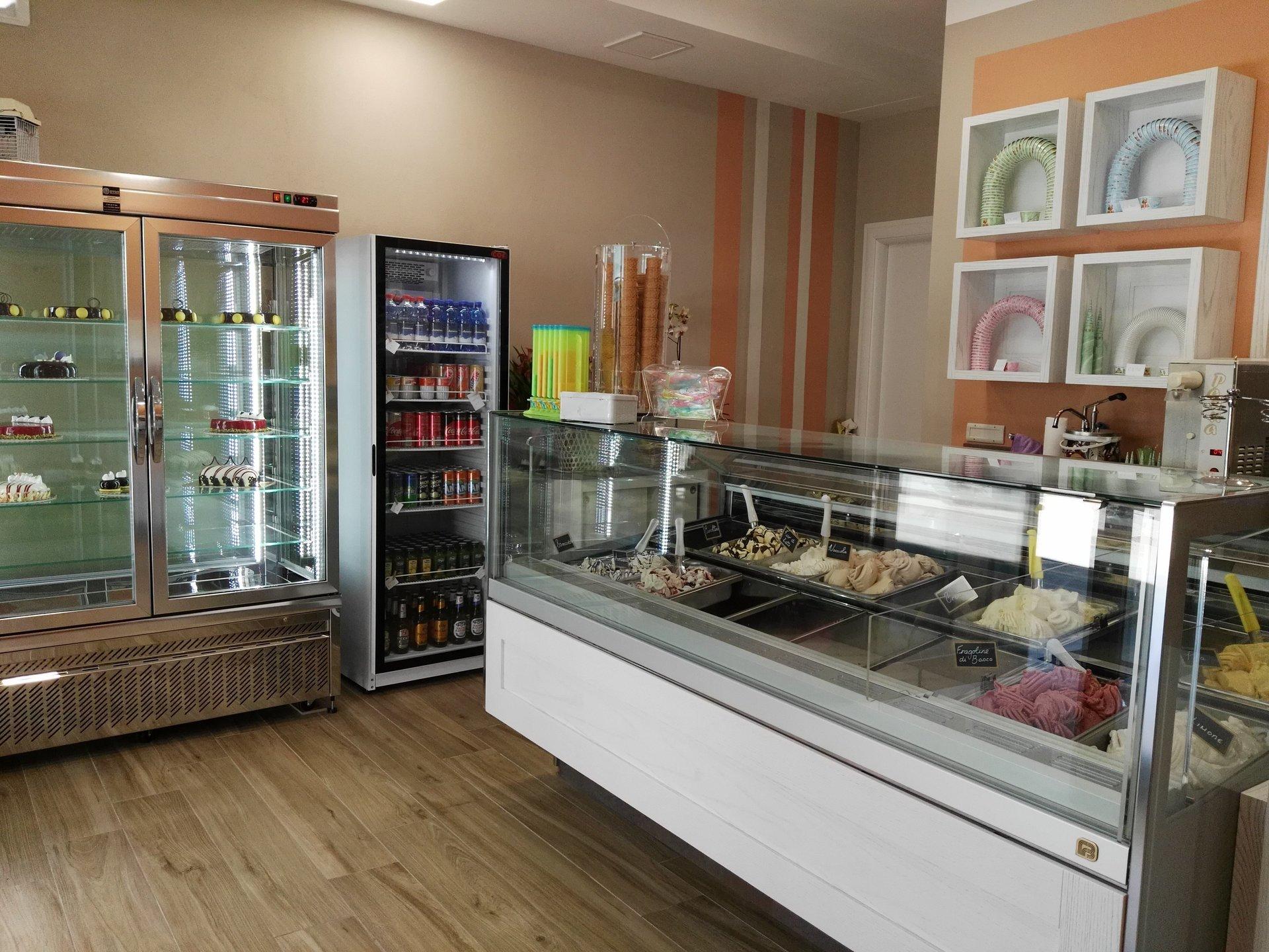 Vista laterale interno gelateria con banco frigo per gelati e frigoriferi verticali