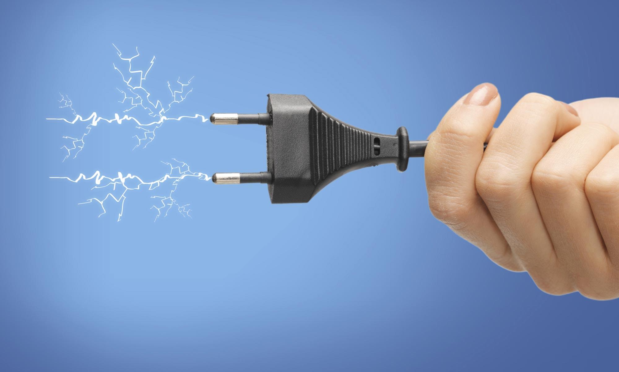 mano che tiene una spina elettrica