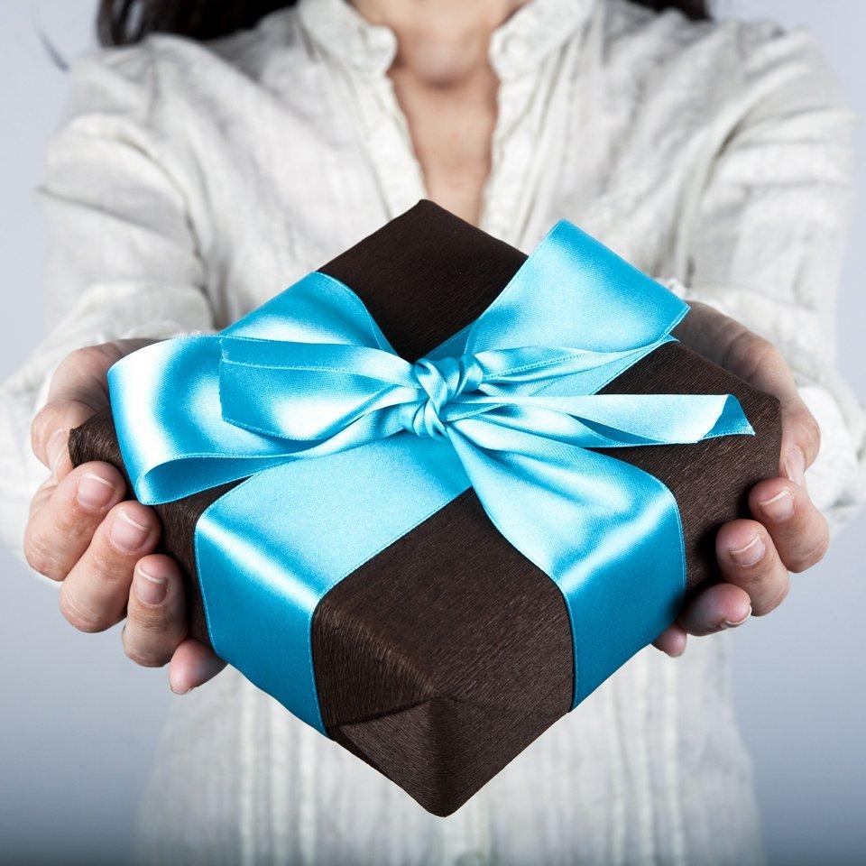 Closeup of a woman's hands giving a present - presents for him concept