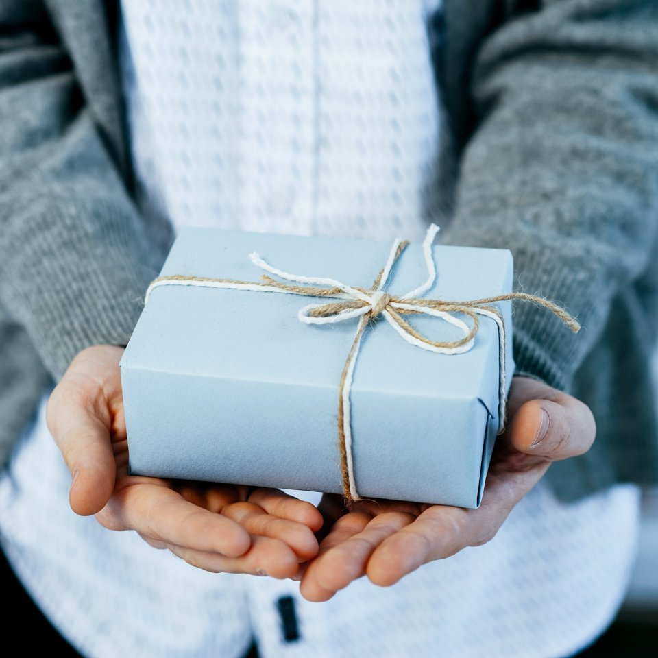 Closeup of a man's hands giving a present - presents for her concept