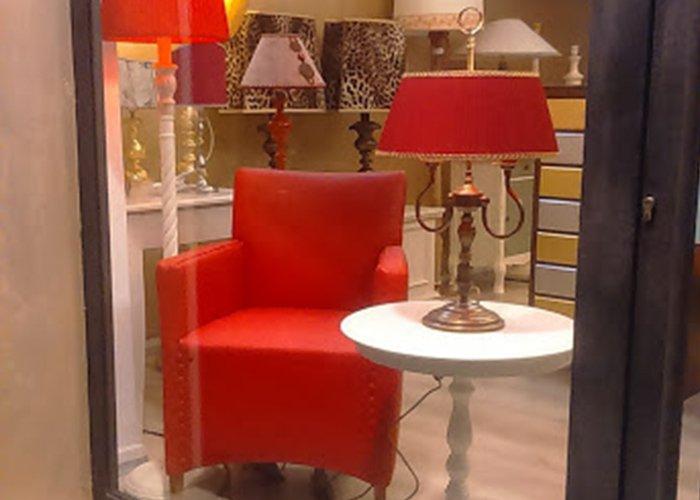 Vetrina con poltrona rossa in pelle, tavolino bianco e abatjour rossa