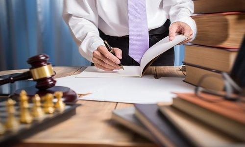 un uomo con un fascicolo aperto e con una penna in mano