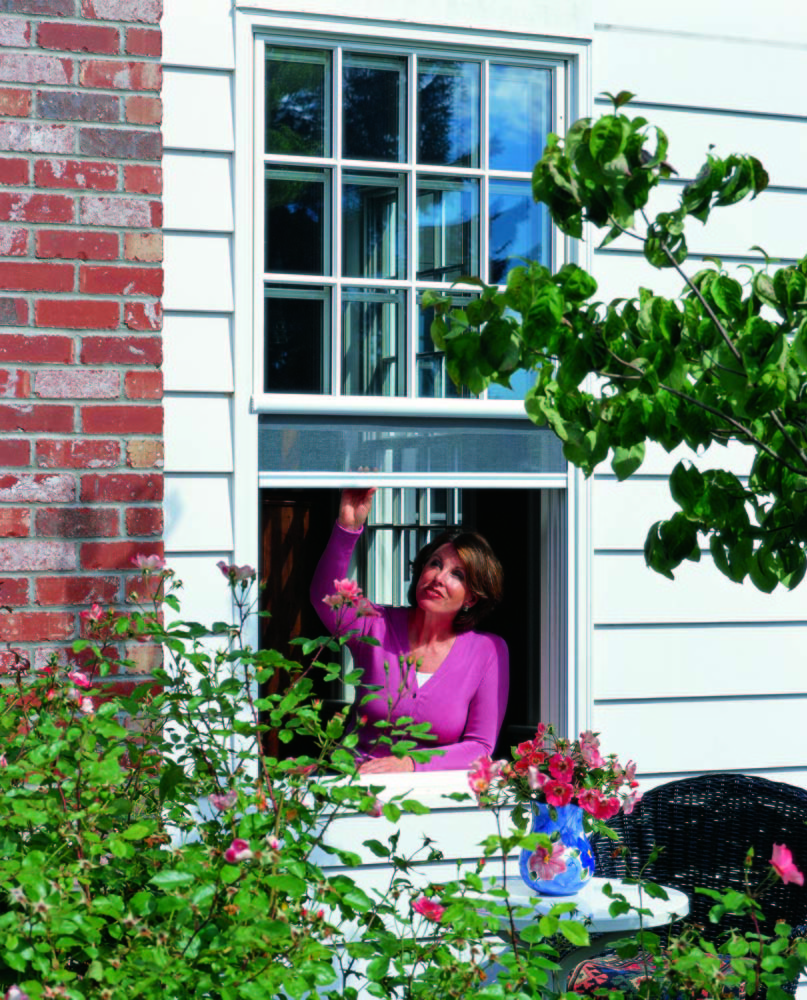 Woman opening window with solar shades in Sonoma, CA