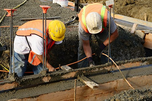 contractors working construction on a building foundation