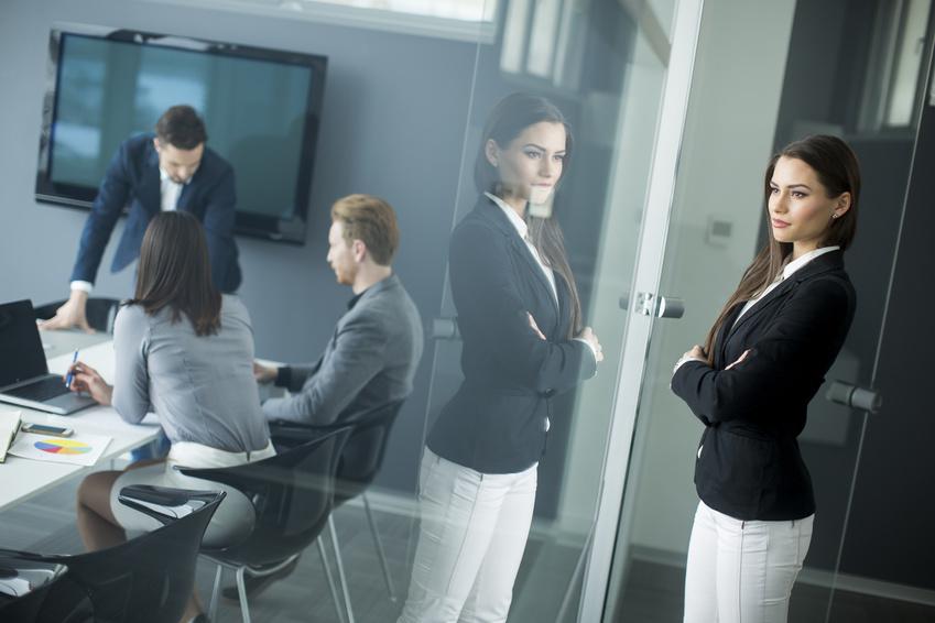 Una donna osserva tre persona in una riunione d'ufficio