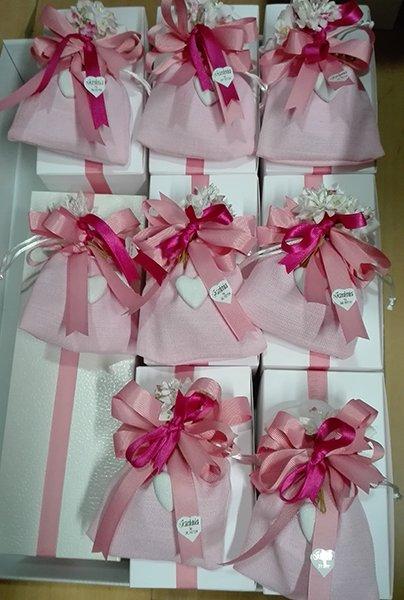 Bomboniere con la scatola di color bianco, sopra dei sacchettini di color rosa legati con nastri di color rosa e fucsia