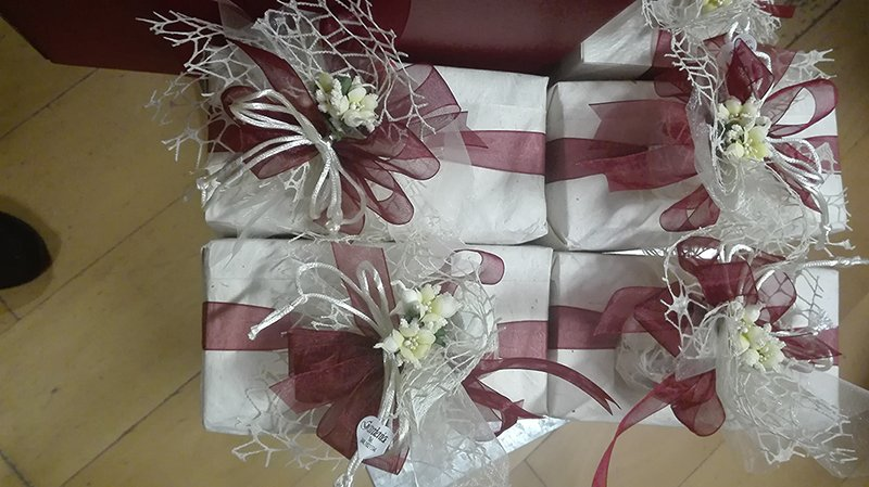 Quattro bomboniere con fiocchi realizzati con nastro di color bordeaux e fiori di color bianco