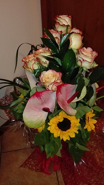 Un bouquet di rose, girasoli e anthurium