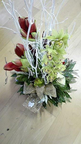 Un bouquet di tulipani di color bordeaux, orchidee verdi, alcuni rametti dipinti in bianco e un fiocco dorato