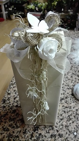 Una bomboniera con la scatola alta e sopra un fiocco grande di color bianco con delle roselline bianche e una raffigurazione di una farfalla bianca