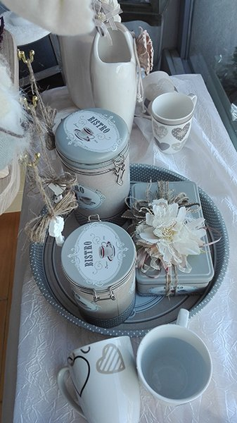 Un tavolino con esposizione delle tazze di caffè grandi di color bianco con disegni di cuoricini, scatole e barattoli nel vassoio con scritto Bistro