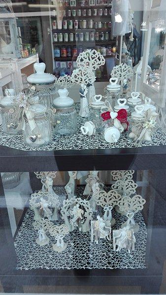 Una vetrina con due mensole con delle bomboniere per matrimonio esposte