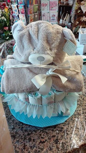 Bomboniere di color azzurro messe a cerchio,sopra un asciugamano di color marrone legato con un nastri bianco e un orsetto di peluche