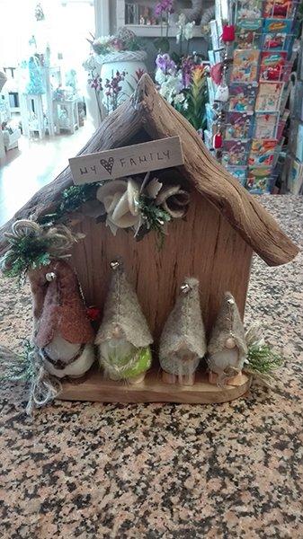 Una casetta in legno con scritto My family e davanti quattro bambole di varie dimensioni con cappellini di stoffa