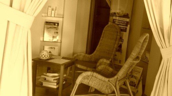vista interna di una stanza con poltroni e tavolo , tenda e tema gialla con arte del benessere