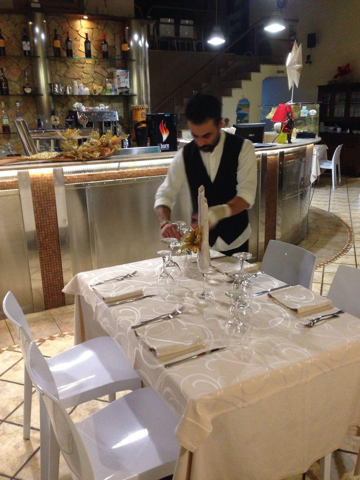 cameriere apparecchia un tavolo