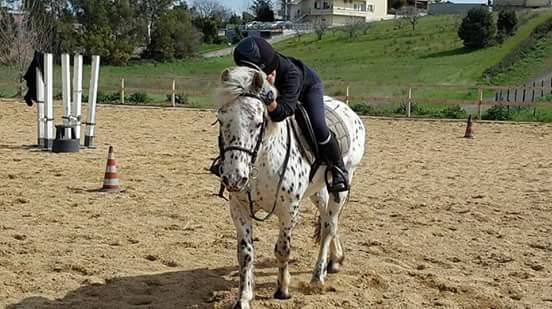 persona al galoppo sopra un cavallo bianco e a macchie nere
