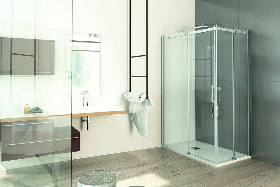 vista interna di un bagno moderno con box doccia in vetro, asciugamano e pavimento in legno
