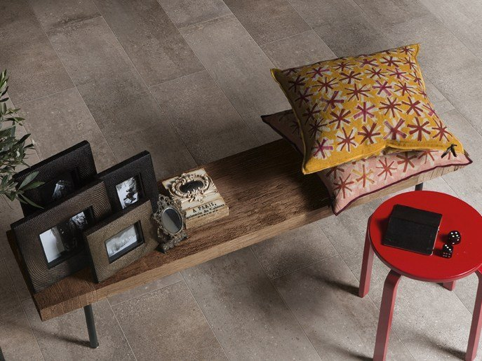 cuscini e cornici su panchina con pavimento in piastrelle in una stanza