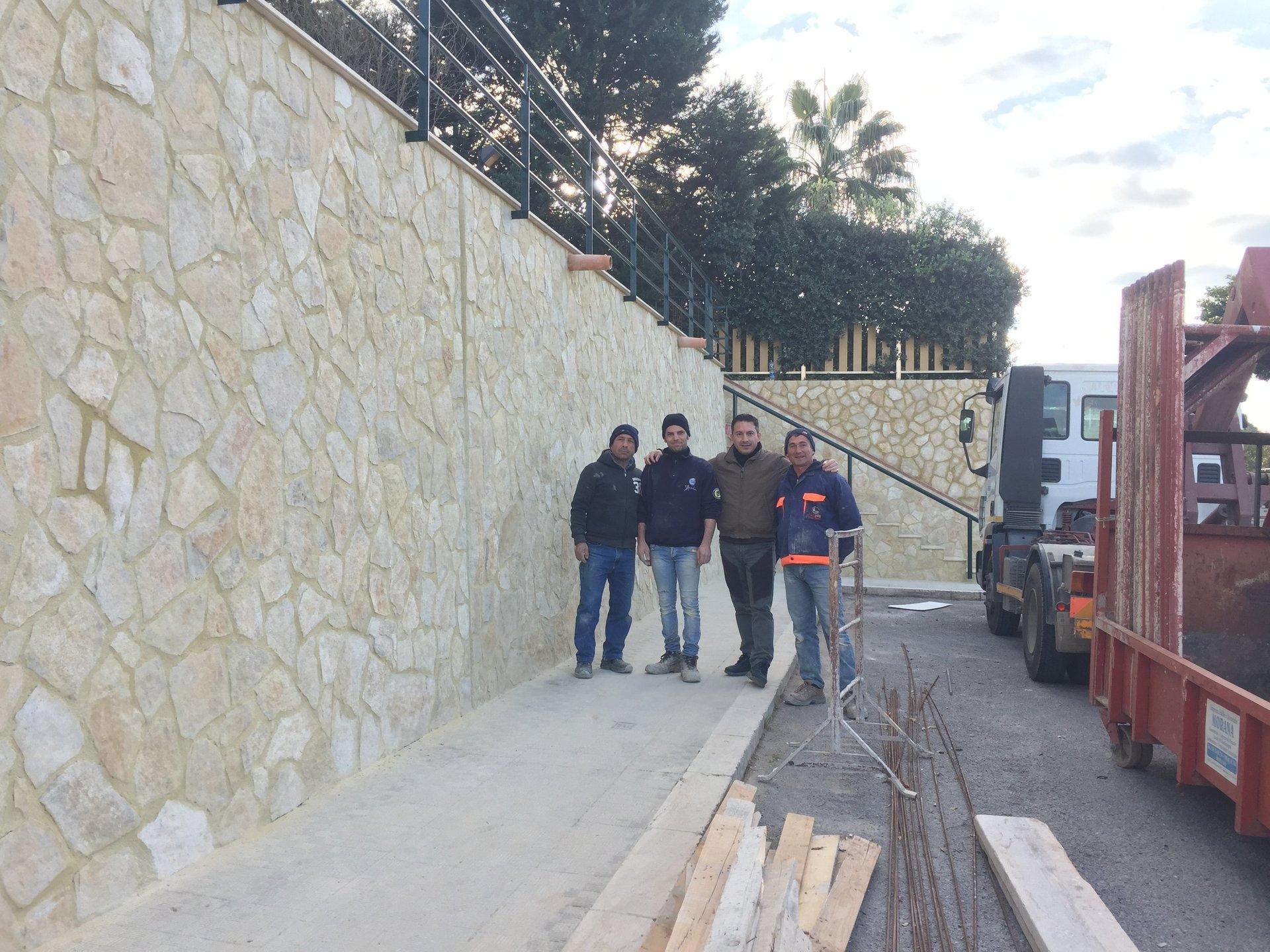 Quattro uomini di fronte ad un muro costruito in pietra