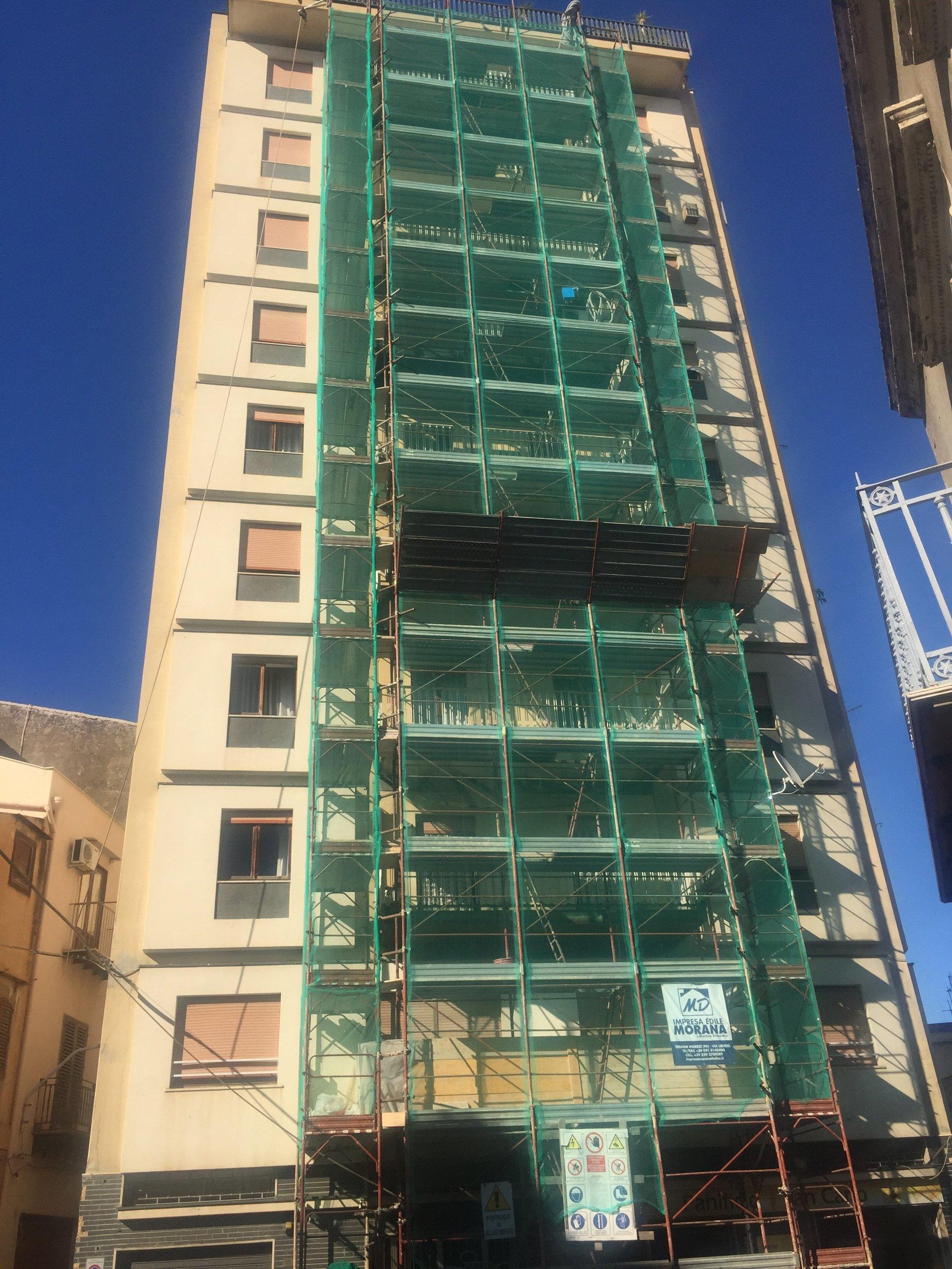 Un palazzo in costruzione con impalcature verdi