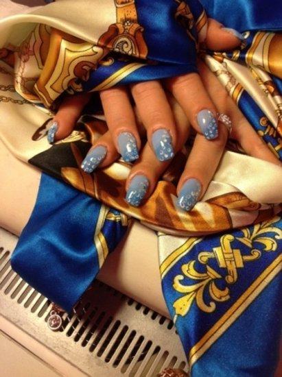 unghie azzurre  sopra una sciarpa colorata