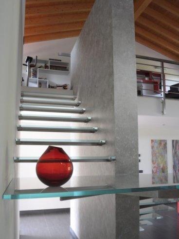 Scale a sbalzo con vaso rosso in vetro appoggiato