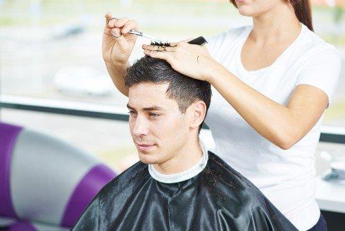 Parrucchiera tagliando il pelo a un giovane