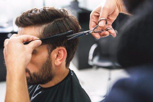 Taglio di capelli a un giovane visto dal laterale