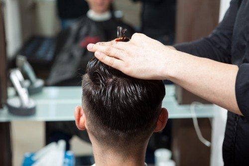 Taglio di capelli a un giovane visto dall'indietro
