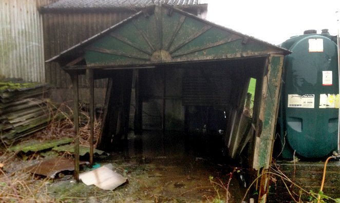 A rusted garage with no door, in a state of complete disrepair