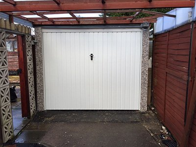 New up and over garage door and repaired concrete post