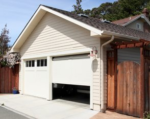 A garage with two sectional garage doors, one in the process of opening