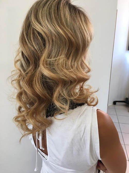 vista laterale di una cliente con capelli mossi e colpi di luce
