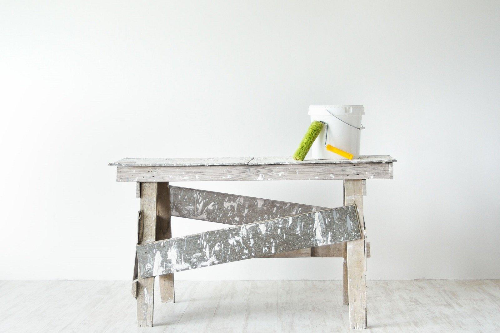 Tavola di lavoro con materiale di vernice, finestra di PVC bianca, radiatore,cartoni nel suolo