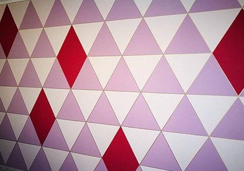 Parete con triangoli violetti e bianchi, rombi rossi  qua e lá