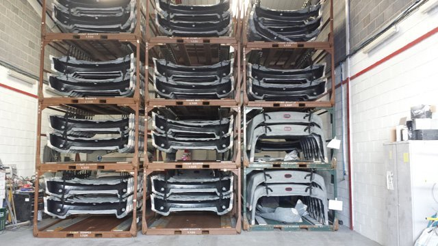 Stacks of car bonnets in pallets
