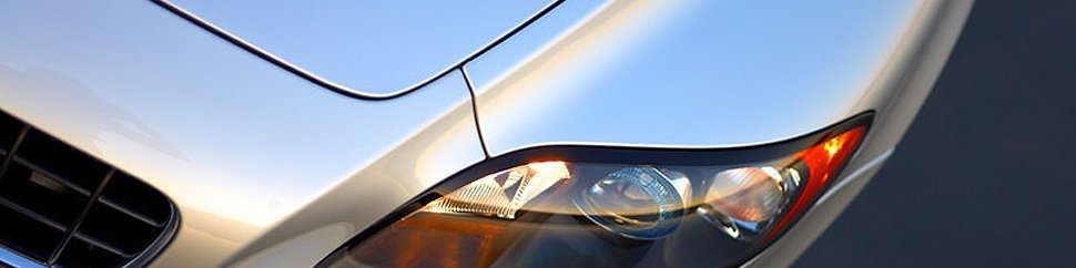 Close up a silver car's bonnet and headlight