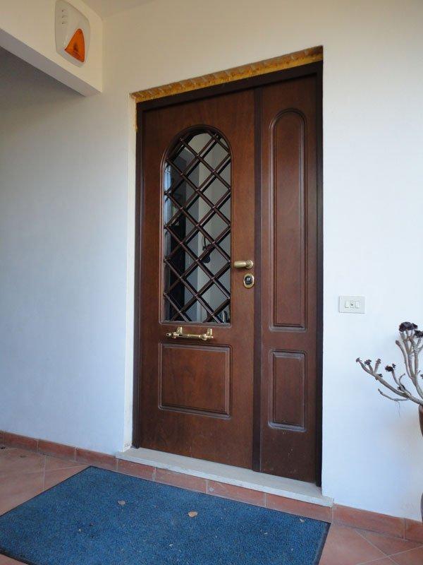 una porta blindata in legno con un vetro e del legno a formare una griglia e di fronte uno zerbino blu
